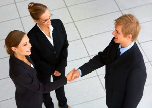 A businesswoman and businessman shaking hands in a hall.
